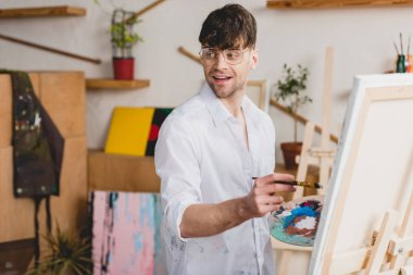 Selective focus of smiling artist in white shirt and glasses painting on canvas stock vector