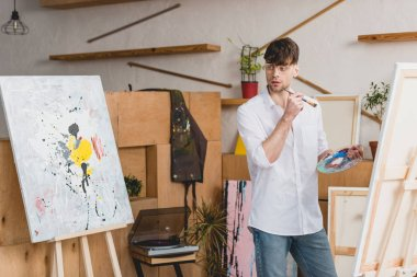 handsome artist with paintbrush and palette looking at painting in gallery