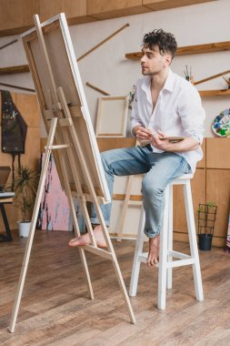 Handsome artist in white shirt and blue jeans sitting at easel in painting studio stock vector