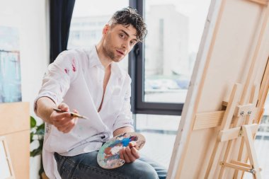 Good-looking artist with palette and paintbrush looking at camera stock vector