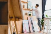 Selektiver Fokus des Künstlers in weißem Hemd und blauer Jeans in heller Galerie