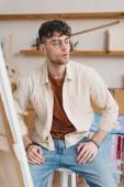 Selektiver Fokus seriöser Künstler in Brillen, die wegschauen