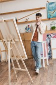 Fotografie handsome artist in blue jeans and pink shirt standing in painting studio and looking at easel with canvas