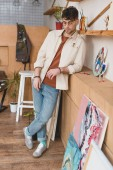pensive handsome artist standing in painting studio and looking down