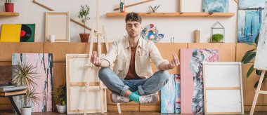 panoramic shot of artist with closed eyes levitating in lotus pose in gallery