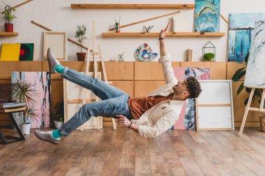 handsome artist levitating over wooden floor in gallery