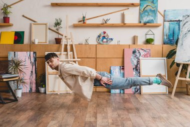 dreamy artist with closed eyes levitating over wooden floor in painting studio
