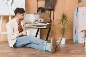 jóképű művész ül a fa padló közelében vinil lemezjátszó