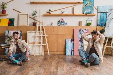 multiple exposure of artist sitting on floor in painting studio