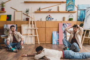 multiple exposure of artist in lying and seating poses in painting studio