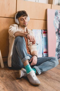 selective focus of handsome artist sitting on wooden floor and listening music in headphones