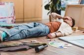 szelektív összpontosít a fáradt művész feküdt a padlón arcát a kezével