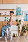 kék farmer etetőszék festés stúdióban ül szép félmeztelen festő