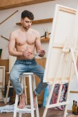 handsome half-naked artist mixing colors on palette while sitting on high chair in gallery