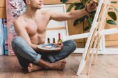 partial view of half-naked artist sitting on floor and painting picture