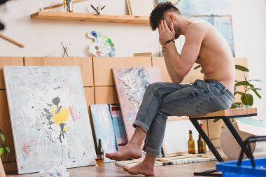 Exhausted artist sitting on chair in painting studio and holding hands on head stock vector