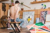 halbnackter Künstler in Blue Jeans sitzt auf Stuhl in Galerie