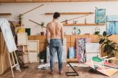 Rückansicht eines halbnackten Künstlers in Blue Jeans, der in einem großzügigen Malatelier steht