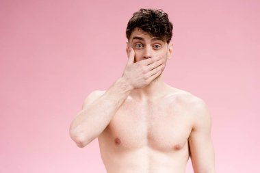 handsome, surprised brunette man covering mouth with hand on pink