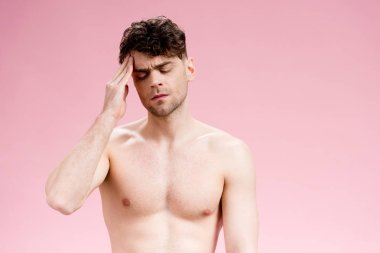 handsome brunette man holding hand near head on pink