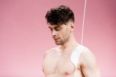 handsome serious man with shoulder in white paint on pink