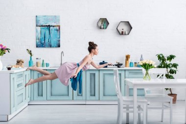beautiful barefoot girl in elegant dress and apron flying in air with pan in kitchen