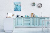 interior of modern bright turquoise kitchen with painting on white brick wall