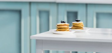delicious pancakes with sugar powder and blueberries in plates on white table