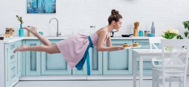 young happy barefoot woman flying in air while serving tasty pancakes