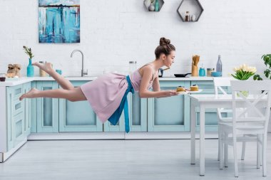 young smiling barefoot woman flying in air while serving tasty pancakes