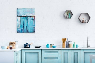 interior of modern kitchen with painting on white brick wall