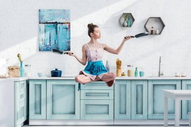 young woman levitating in air in lotus pose with pans in hands