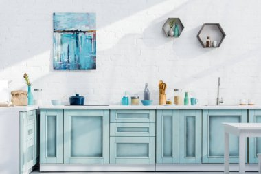 interior of turquoise and white elegant kitchen with kitchenware, decor and sunlight