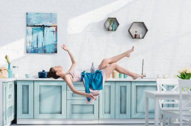 young elegant woman in apron and dress levitating in air in kitchen