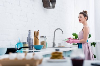 selective focus of young woman in rubber gloves washing dishes in kitchen