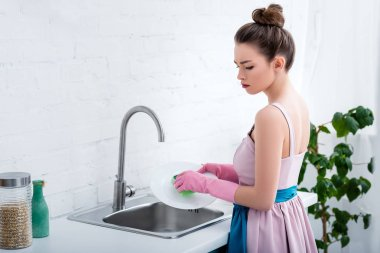 pensive young woman in pink rubber gloves washing plate with sponge in kitchen