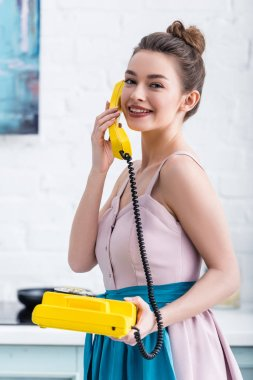 cheerful young woman talking on retro yellow telephone in kitchen