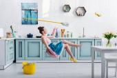 elegante Mädchen in Schürze schweben mit Wischmopp und gelb hochhackigen Schuh während Hausreinigung in Küche