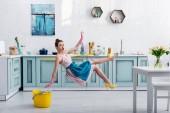 schockiert Mädchen in Schürze schweben mit Wischmopp und gelb hochhackigen Schuh während Hausreinigung in Küche