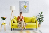 Photo pensive elegant young woman sitting with crossed legs and clenched hands on yellow sofa in living room