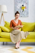 Photo attractive elegant young woman holding book and looking at camera while sitting on sofa