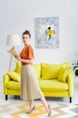 Photo attractive elegant young woman holding book and looking away while standing in living room
