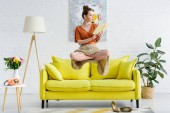 Photo elegant young woman in lotus pose levitating in air while reading book in living room