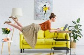 Photo elegant young woman levitating in air and using laptop in living room
