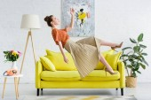 Photo side view of elegant young woman levitating in air in living room