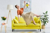 Photo side view of shocked elegant young woman levitating in air in living room