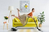 Photo elegant smiling young woman levitating in air and holding vacuum cleaner
