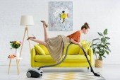 Photo side view of elegant concentrated young woman levitating in air and vacuuming rug in living room