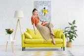 Photo elegant young woman levitating in air and talking on vintage phone in living room