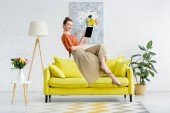 Photo elegant happy young woman levitating in air and showing digital tablet with blank screen in living room